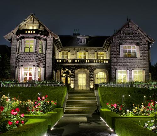 ライトアップされた煉瓦造りの洋館とバラが咲き誇る庭園