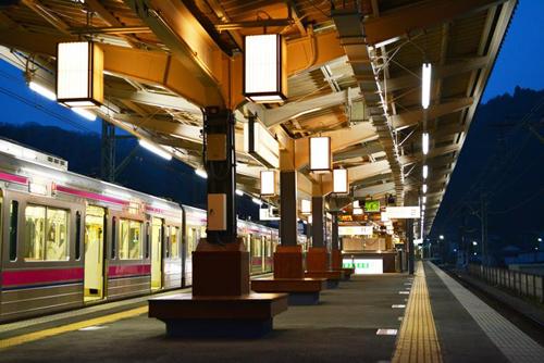 「駅のホーム」 行灯風の照明がホームを優しく照らし、案内板に天狗を入れるなど、高尾山口駅ならではの演出をしている